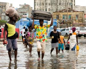 People carry their personal effects after Tropical Cyclone Idai hit, in Beira, Mozambique. Photo: AP