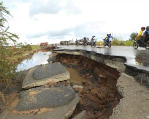 Motorcycles pass through a section of road damaged by Cyclone Idai in Nyamatanda, about 50km from...