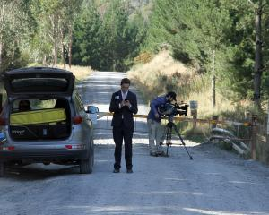 A cameraman from an Australia media channel completes his shooting at Narrowdale Rd in Milburn,...