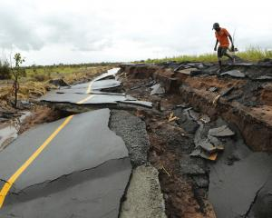 A man passes through a section of the road damaged by Cyclone Idai in Nhamatanda about 50...