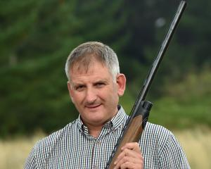 Grant Dodson holds a Beretta sporting-style semi-automatic shotgun, used for clay disc target...
