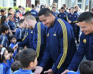 Highlanders Matt Faddes, Shannon Frizell and Sio Tomkinson greet Carisbrook School pupils outside...