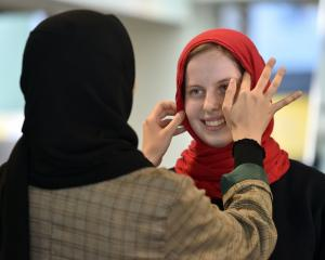Shahad Alismaily puts a hijab on fellow student Maggie Wilson (19) at the University of Otago....