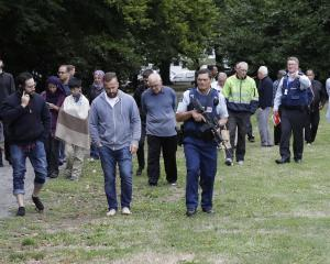 Police escort witnesses away from a mosque in central Christchurch. Photo: AP
