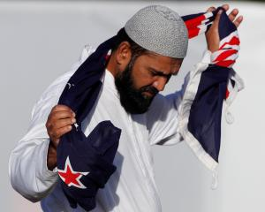 A man carries a New Zealand flag during a burial ceremony for victims of the mosque attacks in...