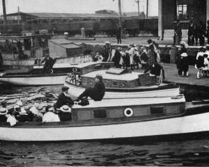 Children from Dunedin orphanages embark on boats for a picnic at Mr A. C. Hanlon's residence at...