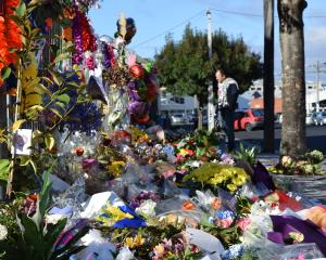 A collection of flowers and messages outside the Al Huda Mosque in Clyde St, North Dunedin. Photo...