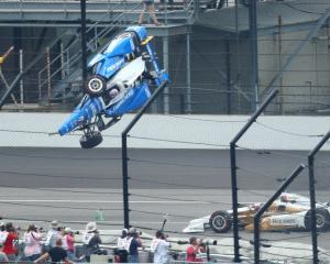 Scott Dixon goes airborne and crashes in front of Helio Castroneves during the race at...
