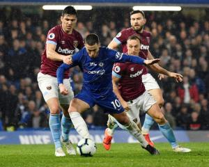 Chelsea's Eden Hazard (C) controls the ball despite the attention of West Ham players. Photo:...