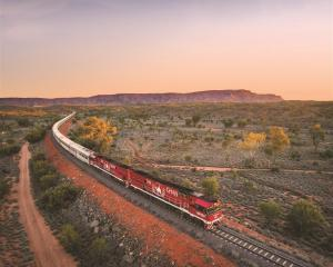 The Ghan heads north from Alice Springs, the MacDonnell Ranges in the background.PHOTO: GREAT...