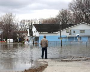 A man looks out at a flooded residential area in Gatineau, Quebec, Canada. Photo: Reuters