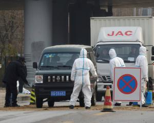 Workers in protective suits man a checkpoint on a road leading to a village near a farm where...
