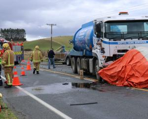 Emergency services work at the scene of a crash between a septic tank truck and a car near...