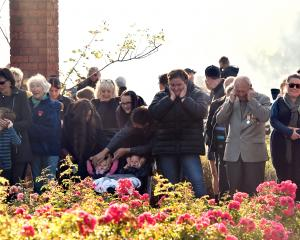 Part of the large crowd at the Mosgiel Anzac Day service at the Memorial Gardens prepare for the...