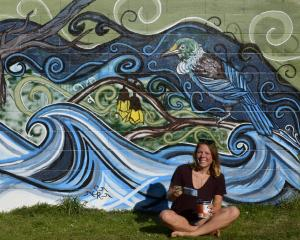 Sarah Raschke sits in front of her near-complete mural in Woodhaugh, Dunedin. PHOTO: GERARD O...