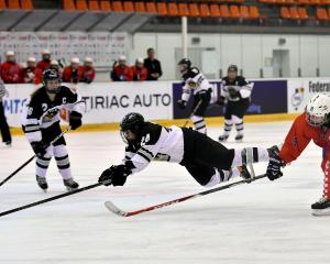 New Zealand player Caitlin Heale, of Otago, flies through the air attempting to reach the puck in...