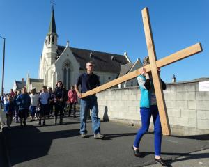 Mark Johnson and Jocelyn Marsh, of Oamaru, carry a wooden cross along Coquet St at the start of ...