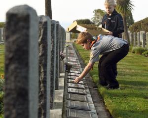 Laying posies on the graves of fallen soldiers at the Andersons Bay Cemetery are Felix Cowan ...