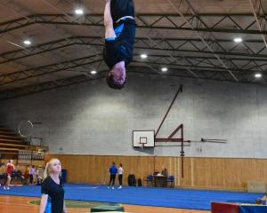Corentin Manti (16) performs a jump on the double mini trampoline as Jess Thompson (21) watches ...