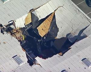 The hole left by the fighter jet after it crashed into the warehouse. Photo: AP