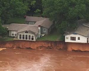 Homes close to a swollen Cimarron River near Crescent, Oklahoma. Photo (via video): AP