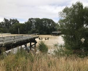 The 50m metre section of bridge over the Mataura River was knocked out by floodwaters. Photo:...