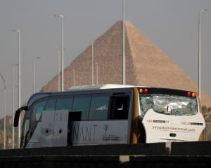 A damaged bus is seen at the site of a blast near a new museum being built close to the Giza...