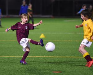 Elsie Munro (9), of Dunedin Tech Flamingos, hoofs the ball forward as Harlow LaHood (9), of the...