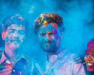 Young people dancing and singing while celebrating the Indian Holi Day. Photo: Getty Images
