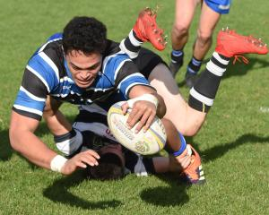 Kaikorai loose forward Christian Lio-Willie goes over to score despite the best efforts of...