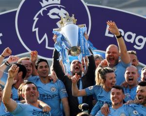 Manchester City manager Pep Guardiola lifts the trophy as they celebrate winning the Premier...