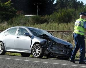 Senior Constable Bruce Dow, of Oamaru, checks a car that was struck by a train at a level...