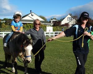 Rome Tangney, on Spice, is led by North Otago Riding for the Disabled helper Margaret Latimer ...