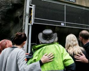 Prime Minister Jacinda Ardern and Andrew Little join grieving families as they gather outside the...