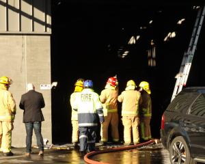 Firefighters inspect damage to the building's interior after the blaze was doused. PHOTO:...