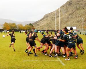 Mt Aspiring College halfback Ethan Kerr clears from a scrum near Wakatipu High School's line...