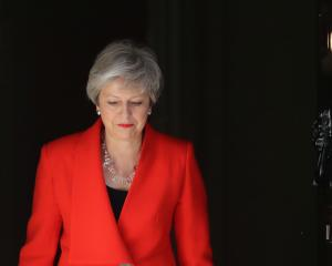 Prime Minister Theresa May, her voice cracking with emotion, said she would resign as...