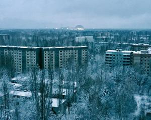 From the roof of a 16-storey apartment building in Pripyat at sunset, a visitor can see what...