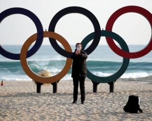 A man takes a selfie in front of the Olympic rings installed on a beach in Gangneung, South Korea...