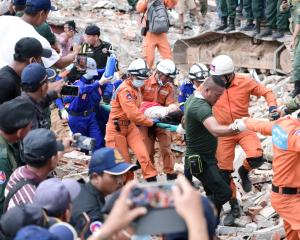 A rescue team carries a wounded worker from the collapsed building site. Photo: Reuters