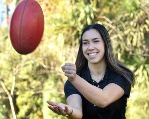 Talented netballer and University of Otago student Killarney Morey plays around with an AFL ball...