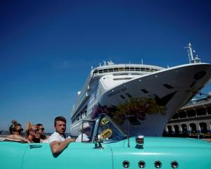 Tourists ride in a vintage car next to a cruise ship docked in Havana. Photo: Reuters