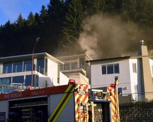 Firefighters at the scene of a house fire in Queenstown this morning. Photo: Stephen Jaquiery