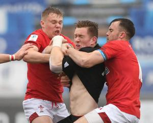 Dallas McLeod, of New Zealand Under-20, is tackled by Ryan Conbeer and Sam Costelow, of Wales...
