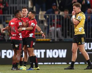 Sevu Reece of the Crusaders celebrates with Richie Mo'unga and David Havili after scoring while...