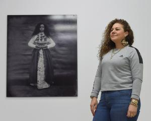 Artist Jasmine Togo-Brisby with one of her works, Ask the Sea, from her Otago Polytechnic...