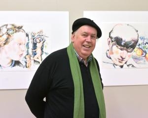 Artist and sexual abuse survivor Michael Haggie shows off two examples of his work at the opening...