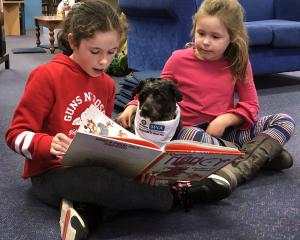 Megan De Cort (12, left) and Emma Magee (6) read to Petal the St John/SPCA Outreach Therapy pet...