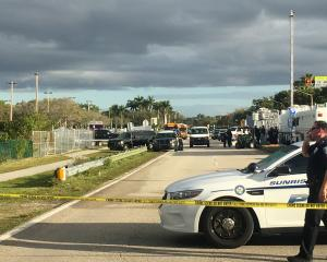 Police patrol the area outside Marjory Stoneman Douglas High School following a school shooting...