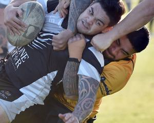Cowboys player Josh Reedy is tackled by Kia Toa Tigers player Joely Penese at the club final at...